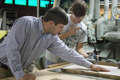 Chad Niman, UK forest products specialist, inspects Garrett Dunn's work. Dunn, a forestry and natural resources student, was among several UK students who volunteered their time and skills to finishing the tabletops.