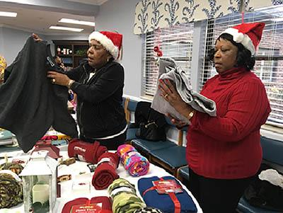 (l-r) Beverly Persley and Gloria Coleman help Pine Meadows residents pick out gifts for themselves and loved ones.