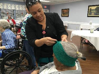 Pine Meadows employee Natasha Smith helps a resident try on a knitted headband.