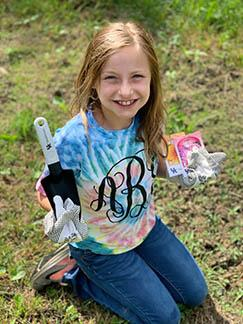 A little girl proudly displays her gardening tools.