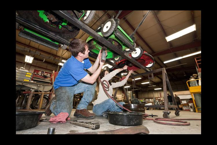 BAE students working on lawnmowers in a previous clinic.