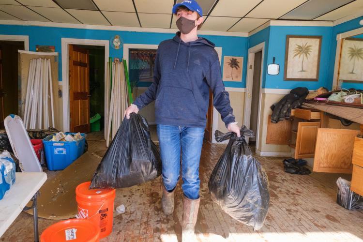 Ty Cheatham, AGR Fraternity member and a freshman agricultural and medical biotechnology major from Adair County, removes trash from a building in downtown Beattyville on March 5. Photo by Matt Barton, UK agricultural communications.