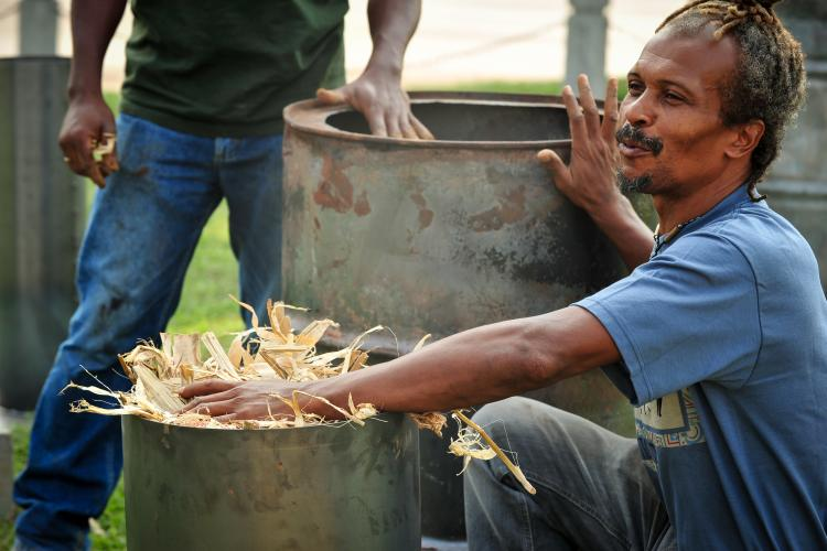 Man demonstrating how to create biochar using plant byproducts