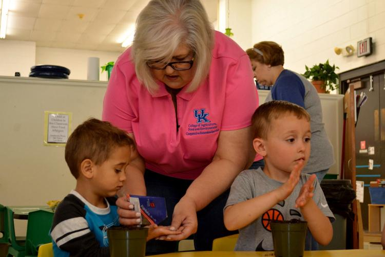 Boyd County horticulture extension agent Lori Bowling gives lettuce seeds to Jamar Higgs, left, as Talin Holbrook looks on. The boys are students at the Early Childhood Learning Center-North in Ashland. Photo by Katie Pratt, UK agricultural communications