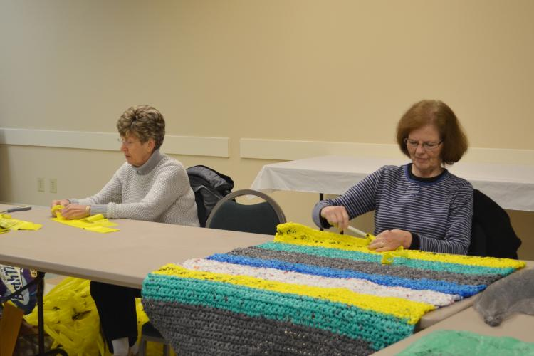"""Boyd County Extension Homemaker Debbie Hoback, left, hooks together pieces of plastic bags to make """"plarn"""" while fellow Extension Homemaker Lana Plymale crochets one of the mats."""