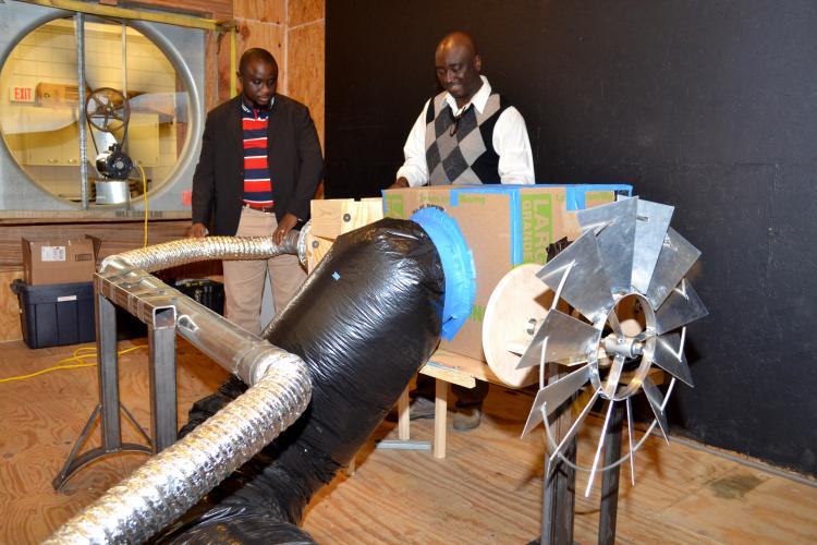 UK assistant professor Akinbode Adedeji and UK doctoral student Francis Agbali look over the wind turbine and grain drying system they developed.