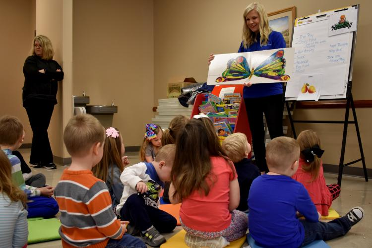 Whitney Morrow reads to young children attending her Play Date program.