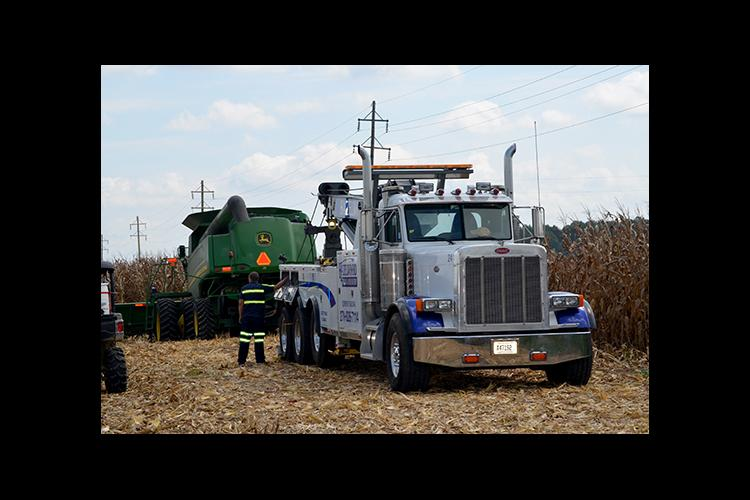 A wrecker removes a combine from a ditch.