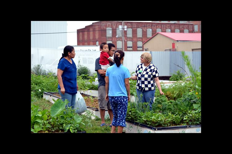 Carol Mark, right, speaks with the Thawng family about the vegetables growing in their garden.