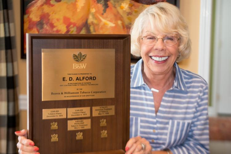 Donna Alford, holding a plaque of Demp Alford's patents
