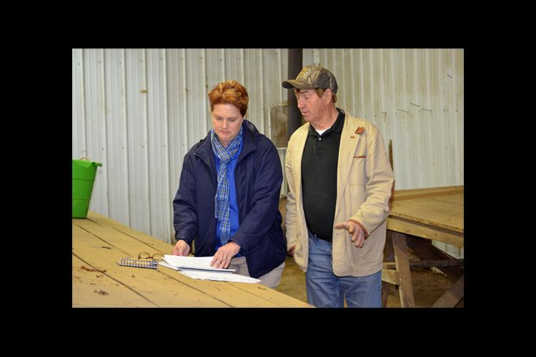 Carol Hinton, left, and tobacco grower Eddie Dyer review Dyer's farm records.