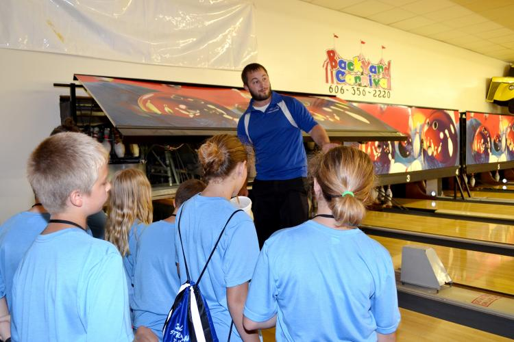 Cody Shannon explains the mechanics behind a his bowling alley to children attending the Community Passport Adventure Camp.  Photo by Katie Pratt, UK agricultural communications.