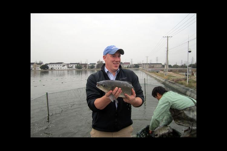 UK doctoral student John Orlowski holds a grass carp at a U.S. Soybean Export Council production demonstration in China.