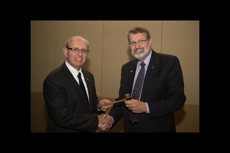 Jimmy Henning, left, receives the gavel from Daryl Buchholz, outgoing ECOP chair.