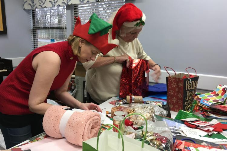 Susan Bradley and Lee Clark wrap presents during a Joy of Giving event.