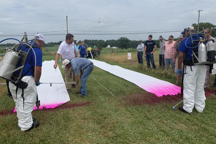 Travis Legleiter, center, explains to producers how nozzle size and boom height affect herbicide drift during the 2019 Spray Clinic. Photo by Lori Rogers, UK KATS coordinator.