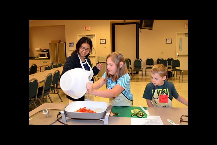 Kendra Oo, left, helps Marley McKoy and Jacob Miles with their stir fry recipe during Boyd County's Kids Can Cook.