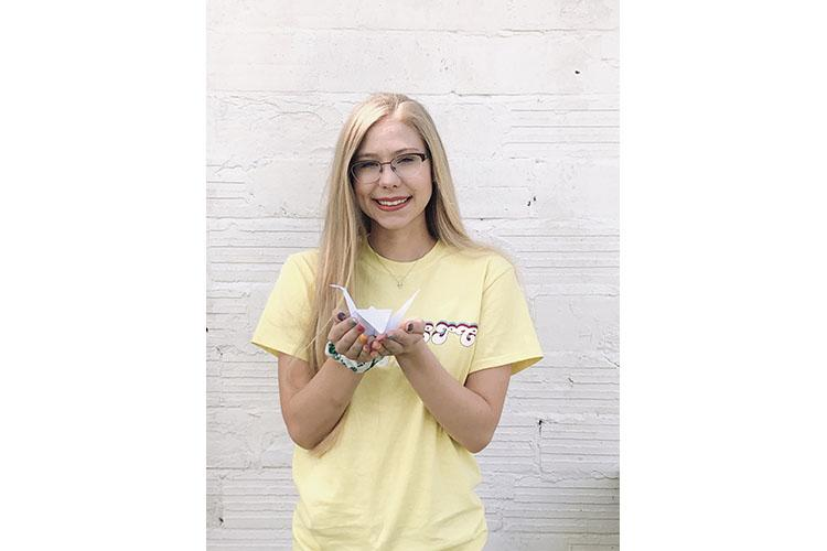Lily Martin, Webster County 4-H'er and State 4-H Teen Council member, poses with one of the paper cranes she has made. Photo courtesy of Lily Martin.