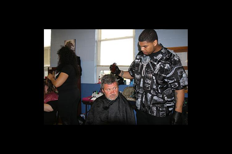 Brandon Merriweather cuts the hair of one of the men who came to the event at the New Life Day Center.