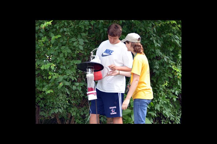 Caleb Mass, left, and Kyndall Dye, students in UK entomologist Grayson Brown's laboratory, install mosquito traps in Lexington.