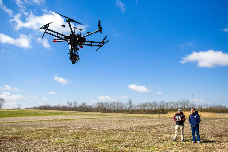 Joshua Jackson, UK assistant professor, and Shawn O'Neal, UK graduate student fly a drone at one of UK's farms. Photo by Matt Barton, UK agricultural communications.