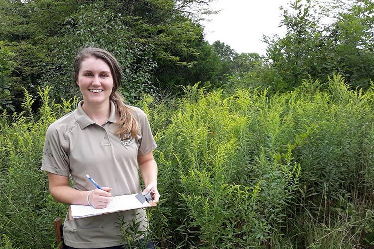 Michaela Rogers standing in a woodland meadow
