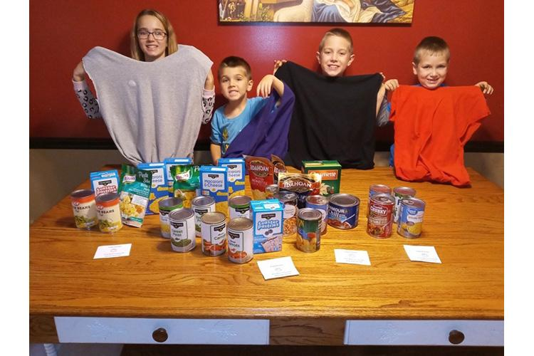 Nelson County 4-H'ers and siblings Brooklyn, Trenton, Colton and Easton Hunt display the upcycled T-shirts they made and the food they collected to put in them as part of the Nelson County 4-H Helping Hands Club. Photo by Shawna Hunt.