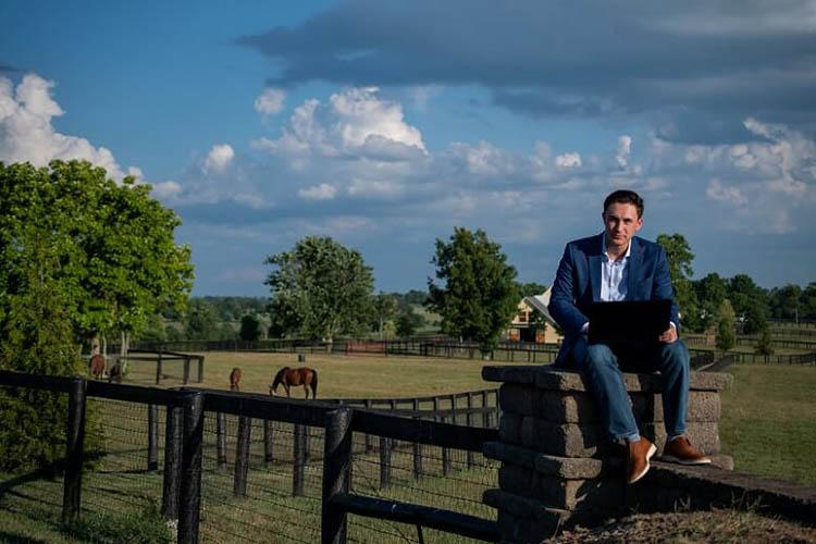 Nick D'Amore uses laptop while perched on a wall at UK Maine Chance Farm