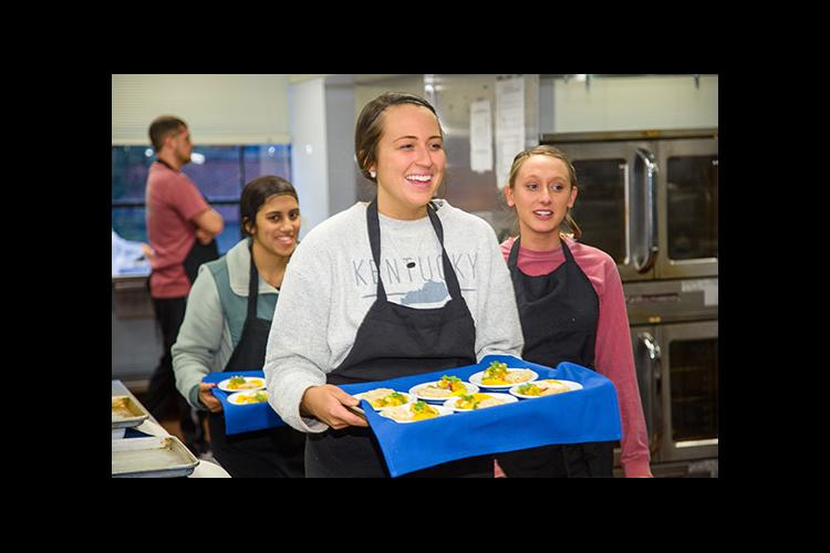 Taylor Runyon, center carries out recipes for taste test panelists at UK. UK students Monica Shah and Hannah Mayse follow.