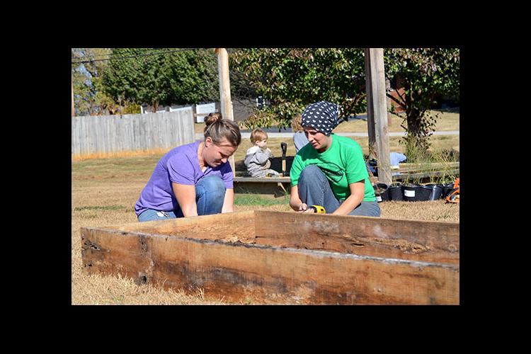 Corina Common and Jennifer Walker construct raised beds at the community garden in Metcalfe County.