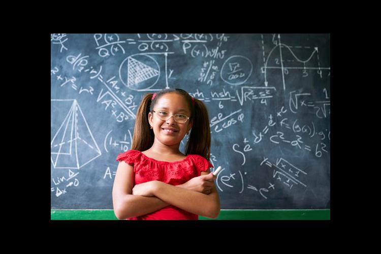 A girl stands in front of a blackboard filled with math equations.