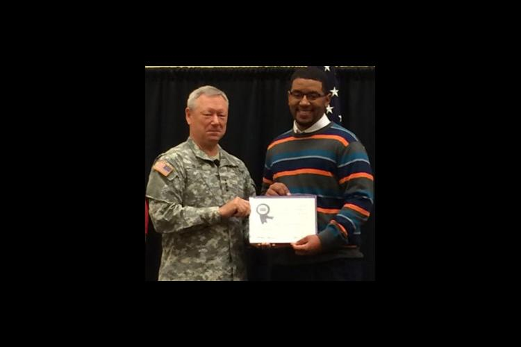 Gen. Frank Grass presents Tyrone Atkinson with the Youth Development Volunteer Award.