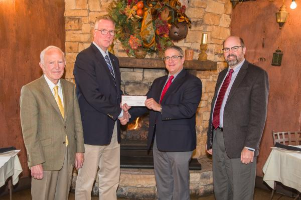Pat Talley (Center Right), Regional Director, U.S. Central Lloyd's America,  gives Dr. David Horohov (Center Left), Chair, Department of Veterinary Science,  a check on behalf of Underwriters at Lloyd's, London to support publication of the Equine Disease