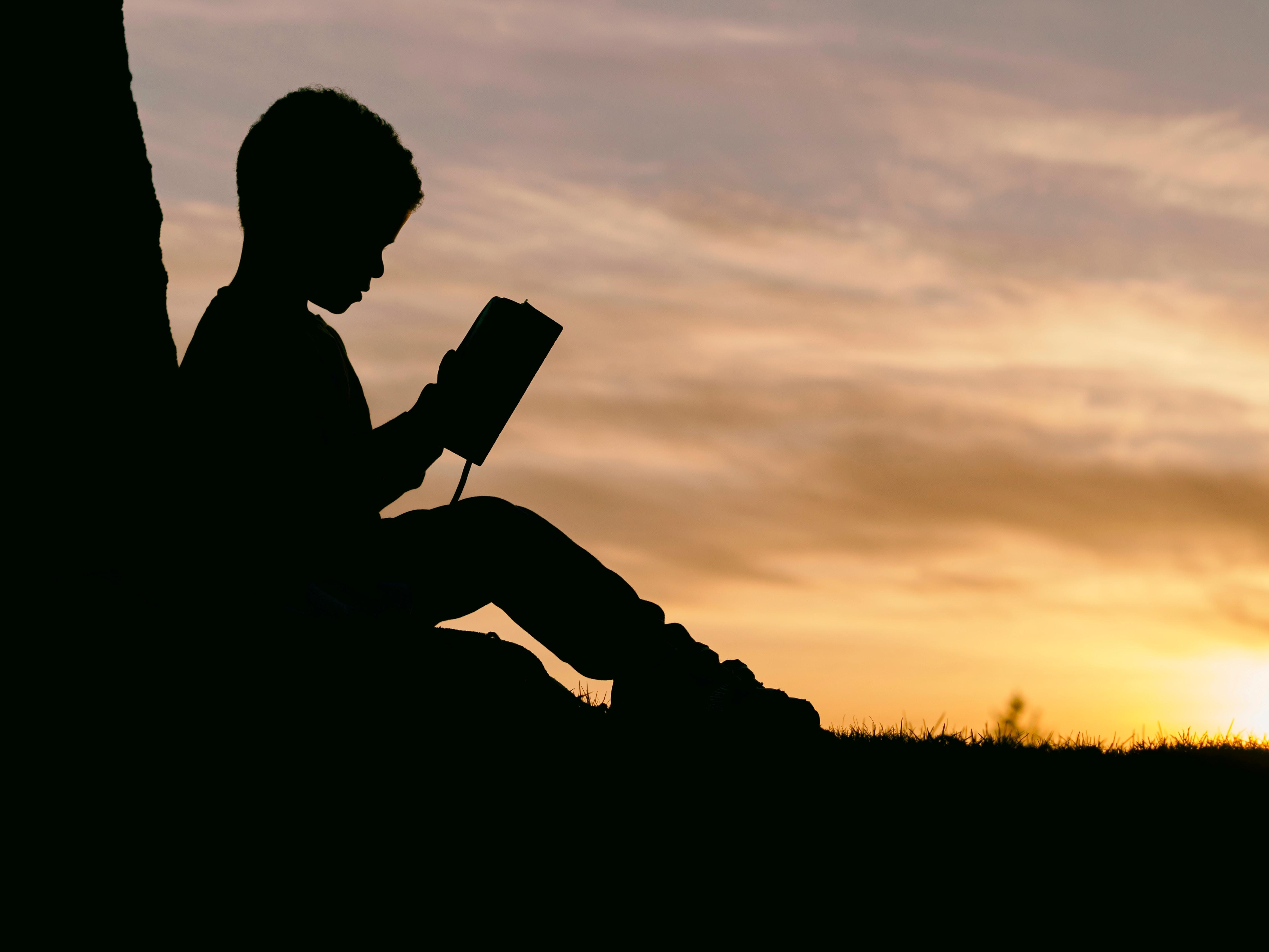 Silhouette of child reading a book outdoors. Photo by Aaron Burden, Unsplash.