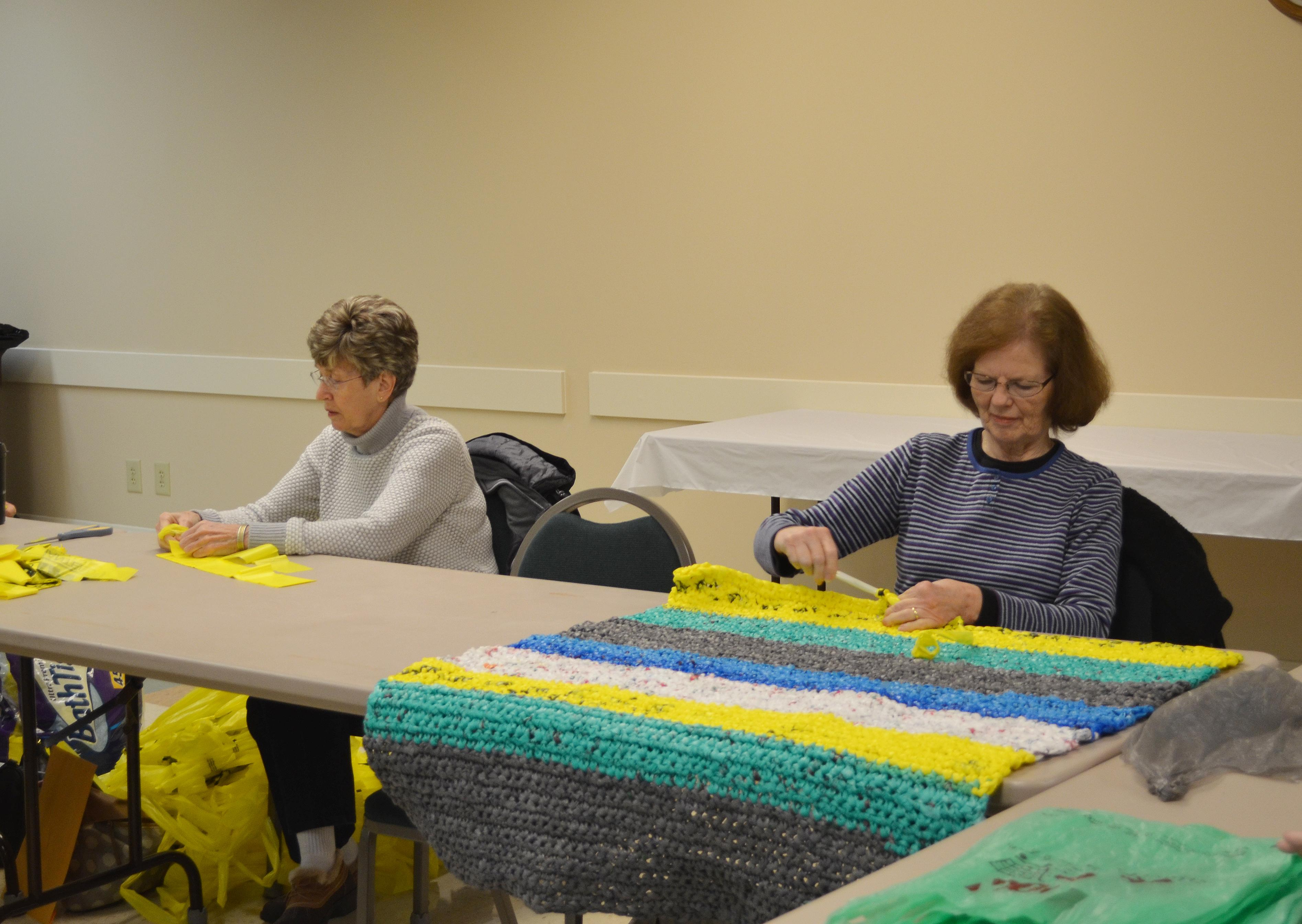 "Boyd County Extension Homemaker Debbie Hoback, left, hooks together pieces of plastic bags to make ""plarn"" while fellow Extension Homemaker Lana Plymale crochets one of the mats."