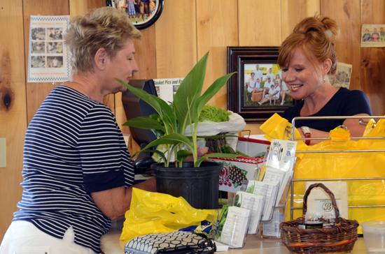 CSA member Donna McMurtrie,left, picks up her weekly share from Cathy Stempien at Brumfield's roadside market.