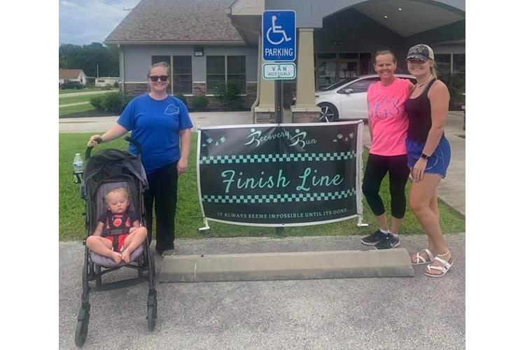 Tinley Creech, Darian Creech, Connie Campbell and Ashton Burks pose by the finish line after completing the virtual 5K as part of the Wolfe County Addiction Recovery Week.  All are members of the same household. Photo provided.