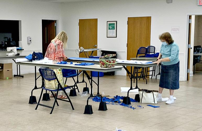 Extension Master Clothing Volunteers Ruby Hord, left, and Leoma Rigdon cut fabric to make surgical gowns.  Photo courtesy of Mandi Broderick, Lewis County family and consumer sciences extension agent.