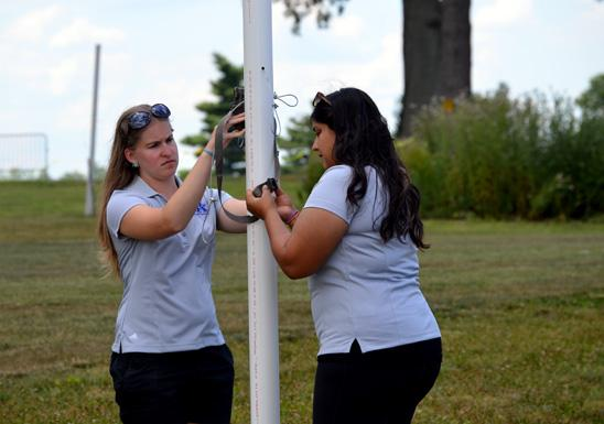 Diana Miller, left, and Abi Saeed of UK tie a wild game camera on the boundary of the turf entomology research plot.