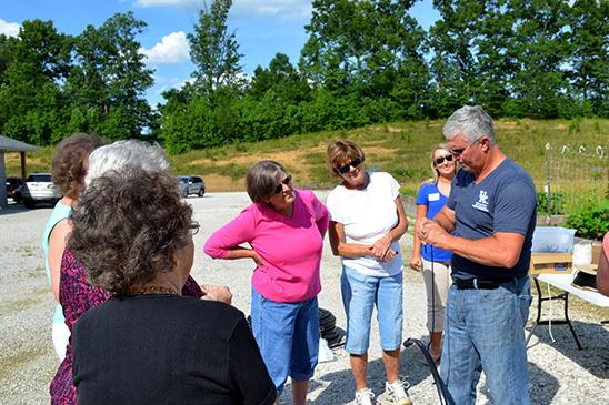 Ted Johnson, Lee County extension agent, shows participants at his raised bed gardening workshop how to install irrigation.
