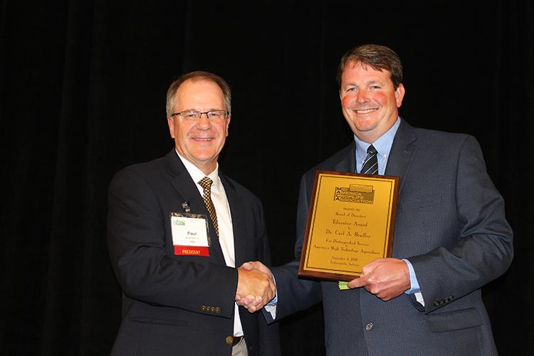 MACA president Paul Edsten presents UK's Carl Bradley with the association's Educator of the Year Award at its annual conference in Indianapolis. Photo provided by MACA.