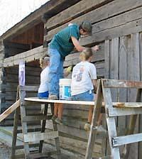 people cleaning cabin exterior