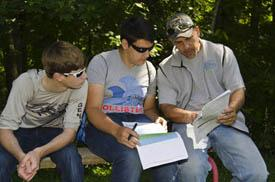 three students studying in woods