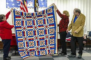 people holding quilt