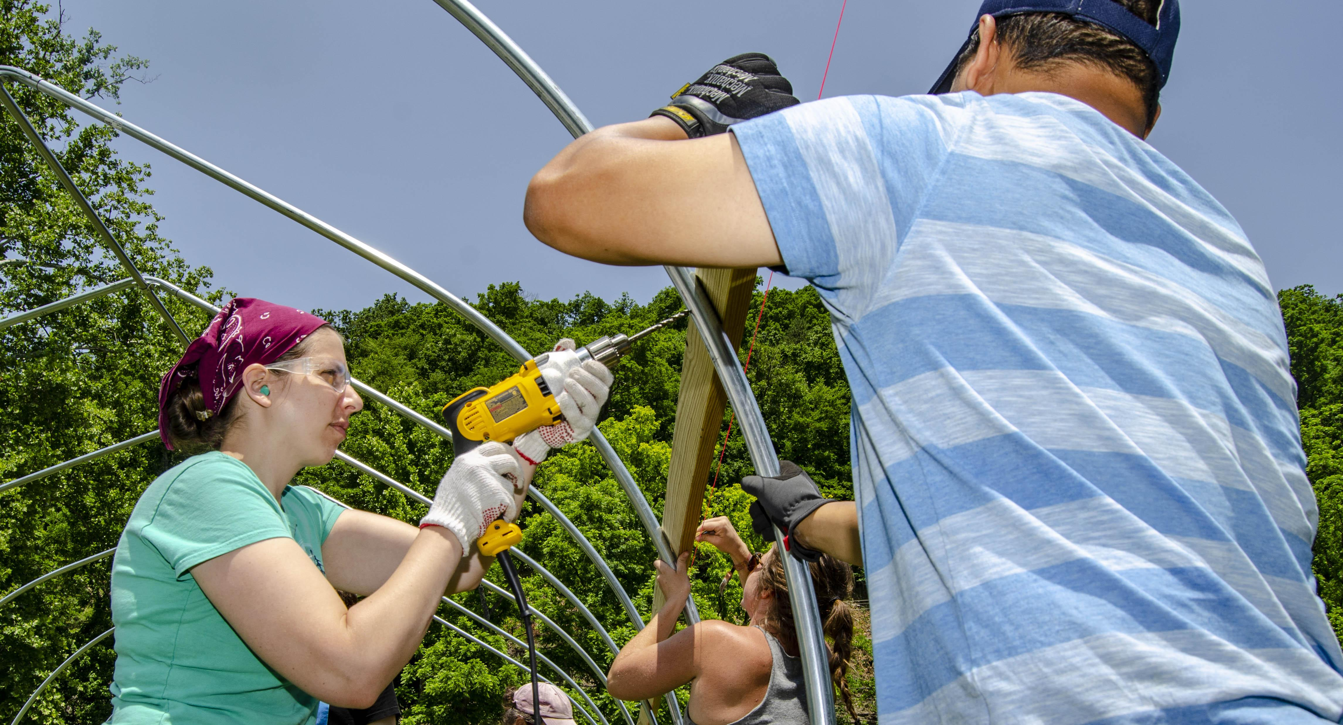 Students from UK, University of Minnesota and Kansas State University construct a high tunnel at the Hindman Settlement School in Hindman, Kentucky.  Photo by Carol Lea Spence