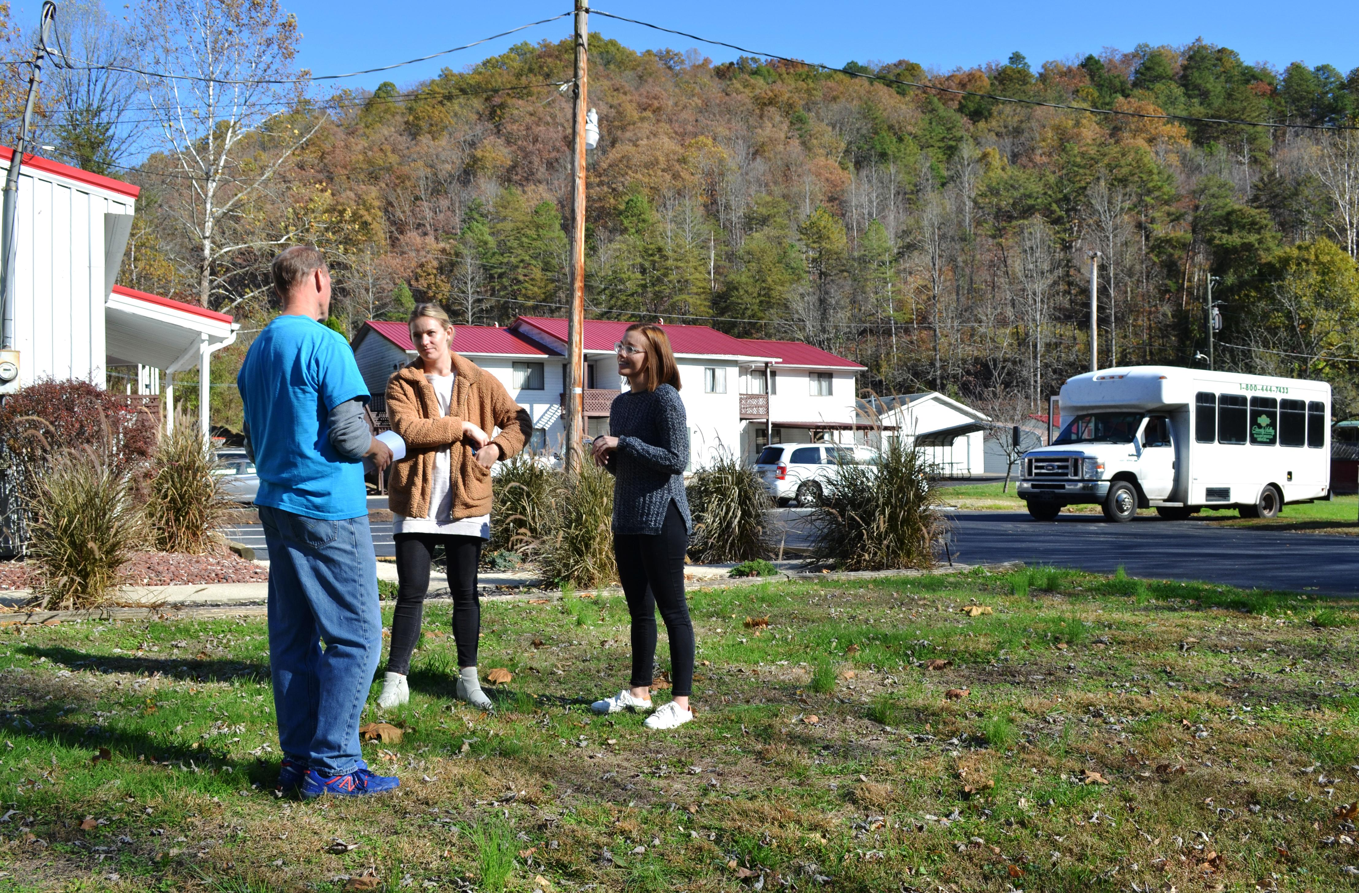 Rachel Gillespie, left, and Emily DeWitt, UK extension associates, talk with Bill Zuidema outside of Appalachian Reach Out in Martin County.  Photo by Katie Pratt, UK agricultural communications.