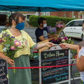 Shelby Wheeler of Bellaire Blooms helped a customer with flowers at the Lexington Farmers Market.  Photo by Matt Barton