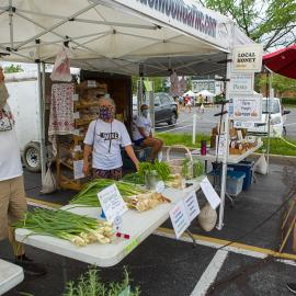 """""""No hugs for a while."""" Leo and Jean Keene, Blue Moon Garlic Farm, practice safe-distancing from long-time customers at the Lexington Farmers Market. Photo by Matt Barton"""