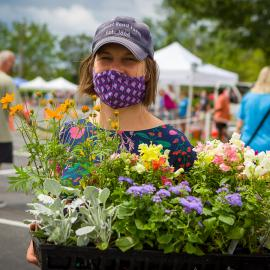 A vendor at the Lexington Farmers Market shows off some of the plants she has for sale, while wearing a mask to protect customers during the COVID-19 pandemic. Photo by Matt Barton