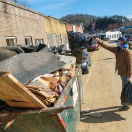 Benjamin Bayless, AGR member and a junior agricultural ecosystems sciences major from Franklin, throws trash into a dumpster in downtown Beattyville. Photo by Matt Barton, UK agricultural communications.